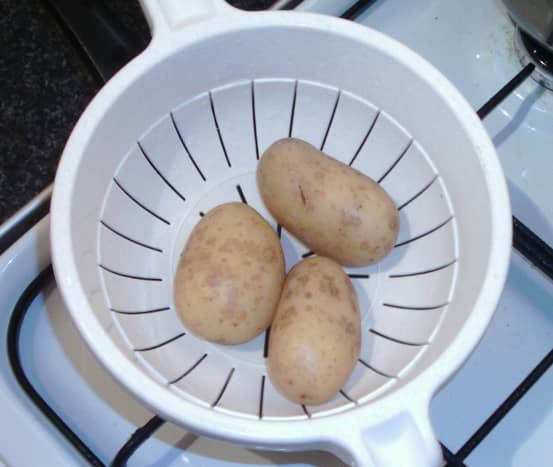 Boiled potatoes are drained and cooled