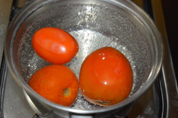 Step one: Boil 4 cups of water. Immerse ripe tomatoes in it. Cover the vessel with a lid. Turn off the stove. Keep aside for 15 minutes.