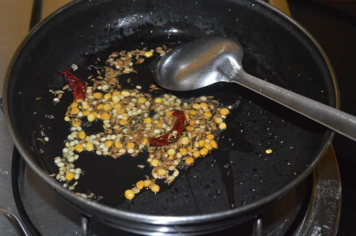 Step one: Make a tempering with oil, cumin seeds, mustard seeds, split chickpeas, white lentils, and broken dry red chilies, as per instructions.