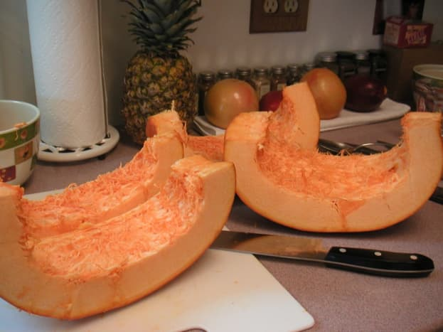 Continue to slice the quartered pumpkin into smaller sections.