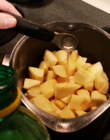 Once apples are peeled and chopped, put them in a pan. Pour lemon juice on top.