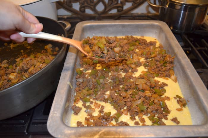 Spread about 1/3 to 1/2 of the corn bread batter into a greased (sprayed) baking pan, then layer on the seasoned, browned meat.