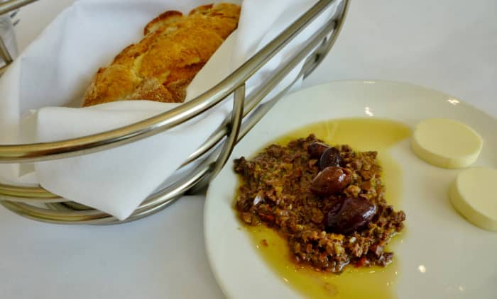 Bread, butter, and olive tapenade is brought to each table.