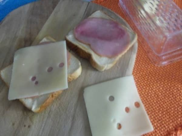 Top the toast with thinly sliced ham and Swiss cheese.