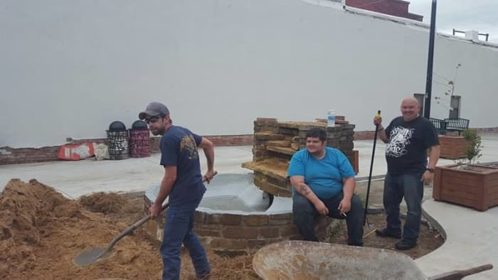 Volunteers helping pour in sand for the brick base.