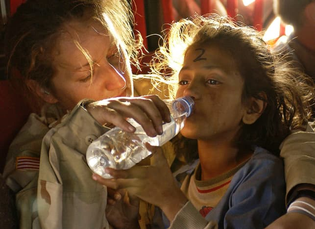 U.S. Army Sergeant Kornelia Rachwal gives a young Pakistani girl a drink of water