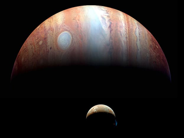 Jupiter and Io photographed by the New Horizons space probe to Pluto, passing by in 2007. (Jupiter is captured in infrared, which maps heat, so the Great Red Spot looks white). Note eruption plume on Io's pole (right).
