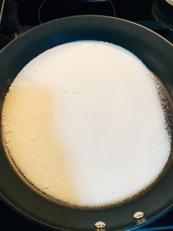 Pour one cup of white granulated sugar into a prepared pan. Heat up the sugar on low heat.
