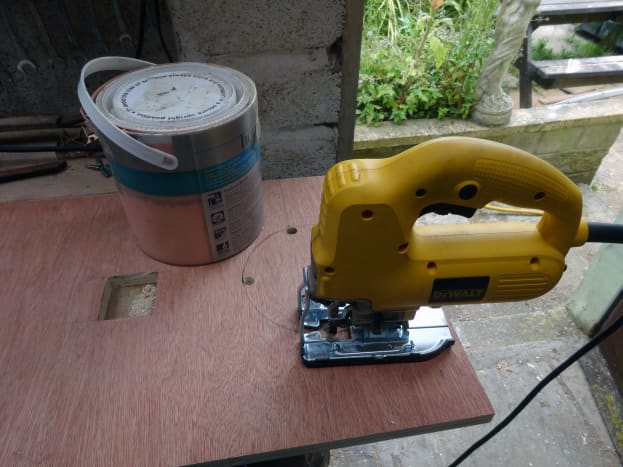 Five-liter (one gallon) paint pot used to mark the cat's play hole, which is then cut out with a jig saw.