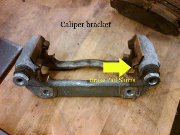 Remove these caliper anti-rattle clips to look for built-up rust restricting brake pad movement. Pads should move freely in the caliper brackets.