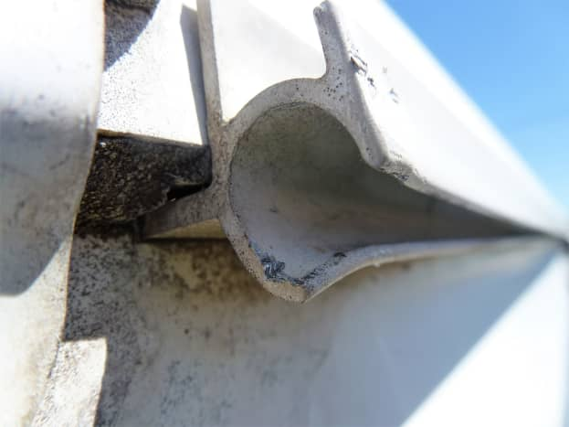 The lower corner of the track was bent down slightly to prevent tearing the new awning.  The upper corner could not be bent with any reasonable force because of the way it was constructed.