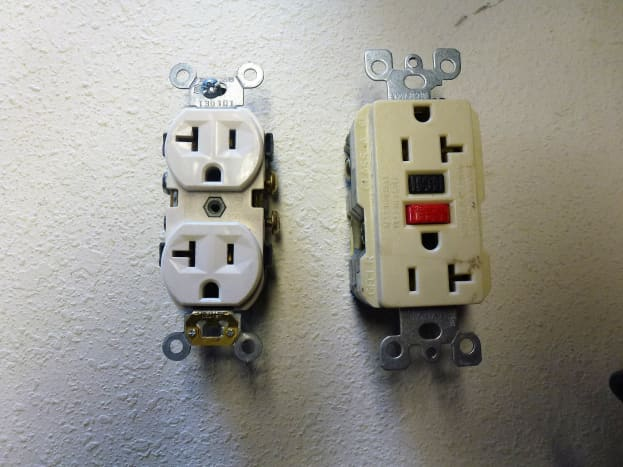 A regular outlet.  The white one will not be acceptable - the ivory one on the right is what you will need.  A common 20 amp GFCI outlet, just like the ones in your kitchen.