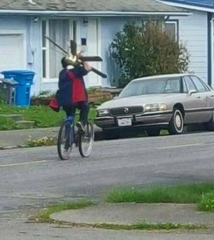 A cyclist carries a ceiling fan.