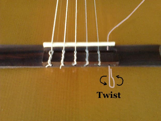 Slide the string through and loop it back on itself then twist several times...