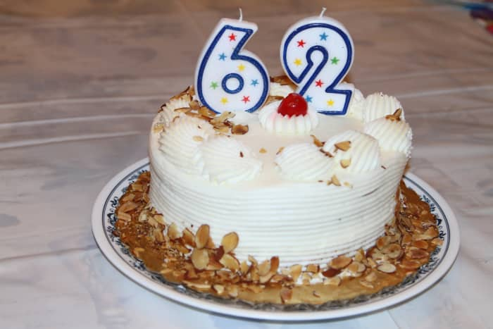 A cake simply decorated with candles, frosting, nuts, and cherries.