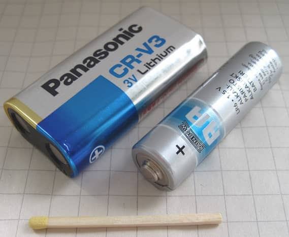 CRV3 3 volt non-rechargeable lithium battery alongside an AA cell for size comparison.