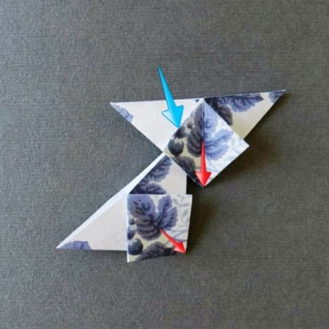 Take two folded tiles and interlock them as shown in photos. Think of one piece in each hand. The point of the piece in the left hand goes under the diamond of the tile in your right hand and meets at the red arrows.