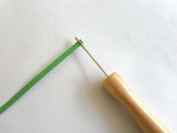 Insert one end of quilling paper into the slit of quilling tool.