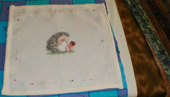 Frame measured and pinned, and the edge of the hedgehog cross stitch protected with a calico binding.
