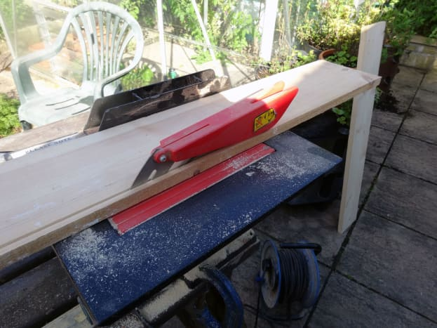 Trimming wood to the correct width with a bench saw.