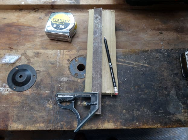 Marking up the base plate to drill the two holes for fitting the wooden pegs.