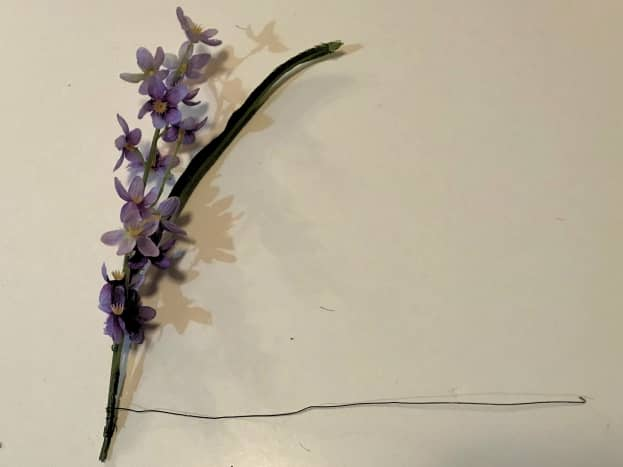 For each flower stem you plan to attach to the handle, remove the lower stem leaves and extra stem length. Cut a foot-long length of craft wire and tightly wrap the bottom of the stem.