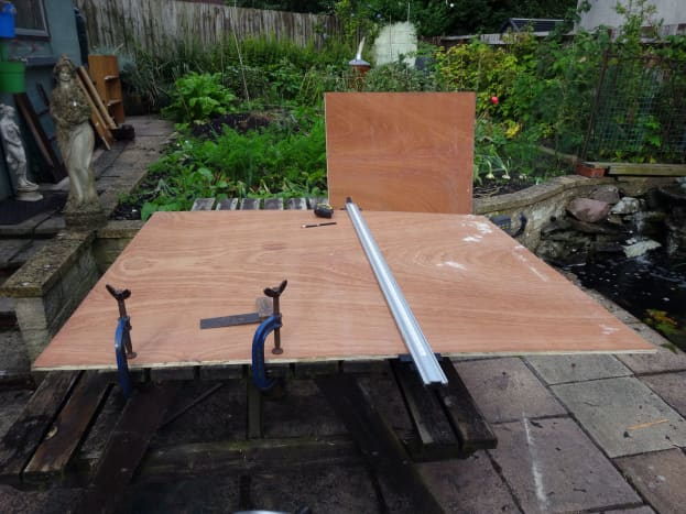 A 4ft x 8ft sheet of 12mm plywood being marked up to cut the sections for the three shelves.
