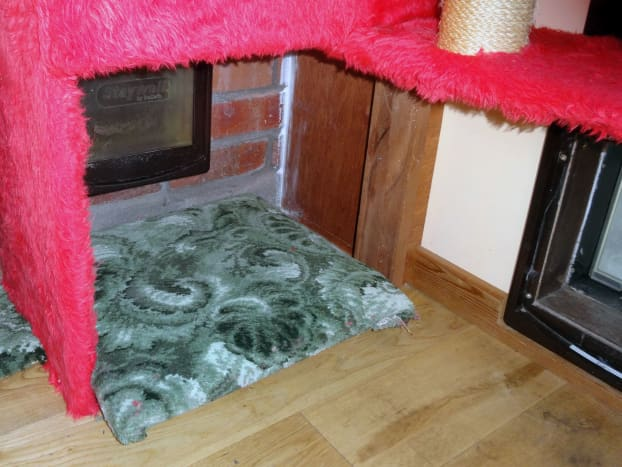 Padded cat flap insulator upholstered in carpet, which doubles as cat bed.