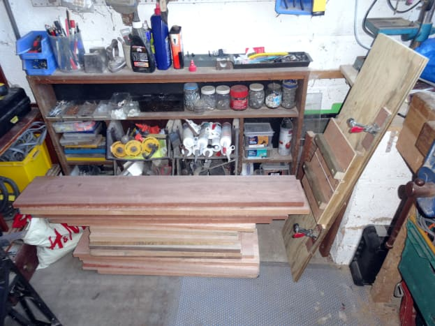 The Meranti planks brought back to Bristol from Portsmouth, England; with a jig on the right my friend made for routing divider slots in the drawers.