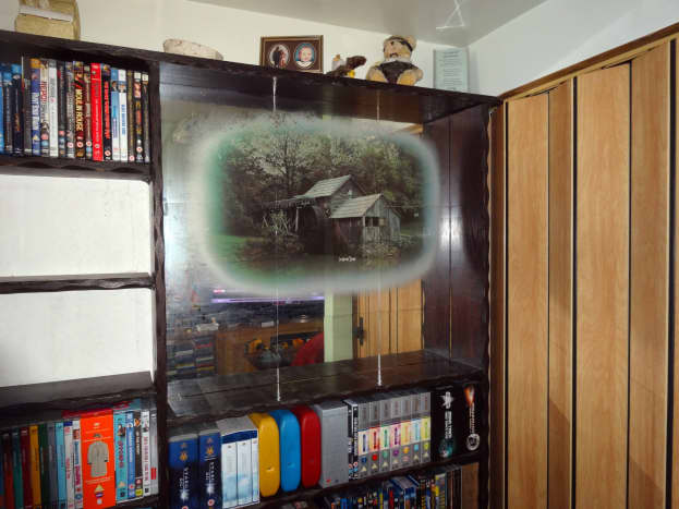 DVDs and Blu-ray discs removed from the area where I would be working to fit the new shelves; revealing the decorative mirrored picture behind.