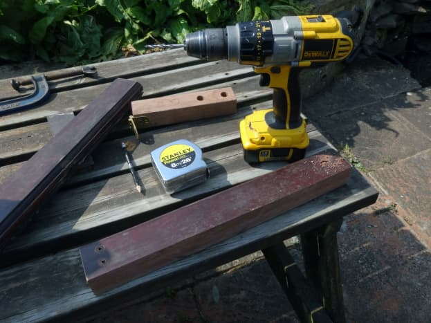 Drilling pilot holes in the arm supports for fitting to the table's side skirts.