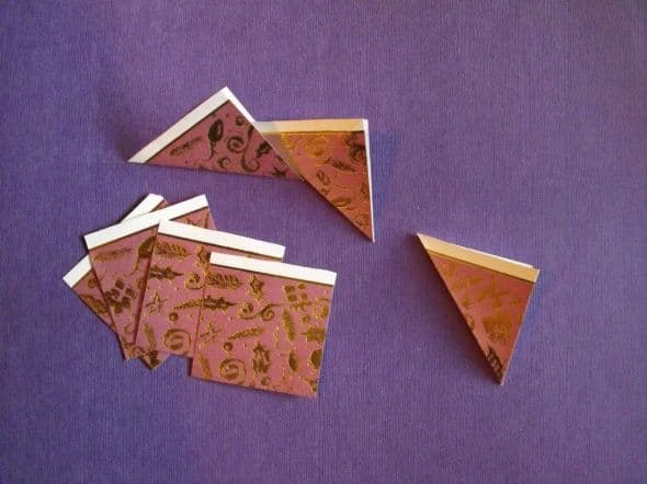 Cut seven two-inch tiles from paper of your choice. Fold the seven tiles in half diagonally, as shown above.