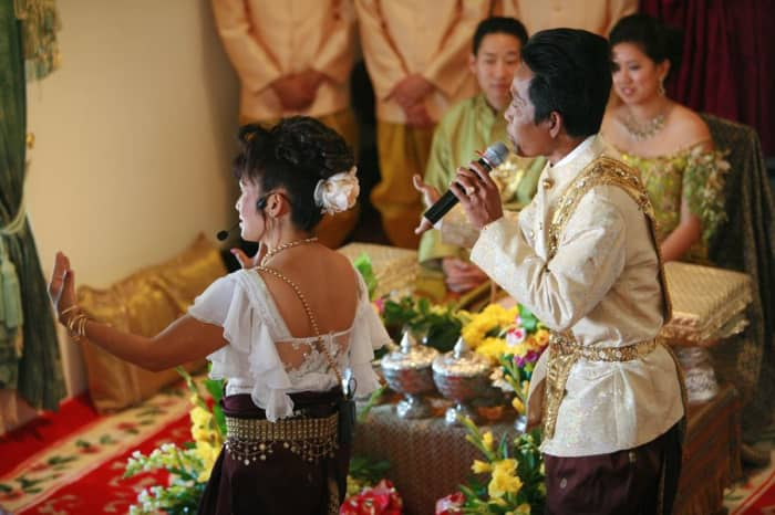 Two Khmer singers, representing heavenly beings, symbolically cleanse the wedding couple of their past.