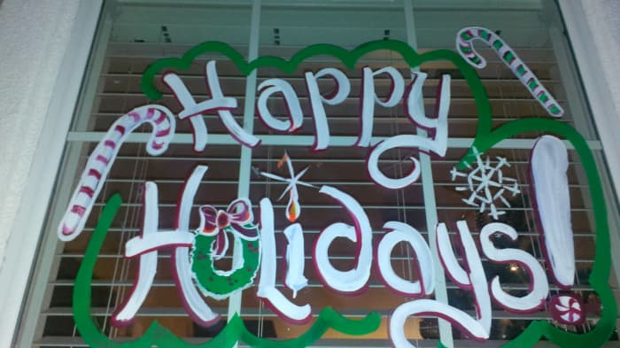 Happy holidays painted on a residential window set.