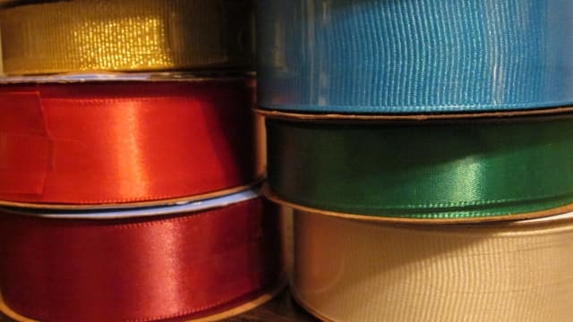 Assorted ribbons with bold color and texture beautifully accent a gift basket.