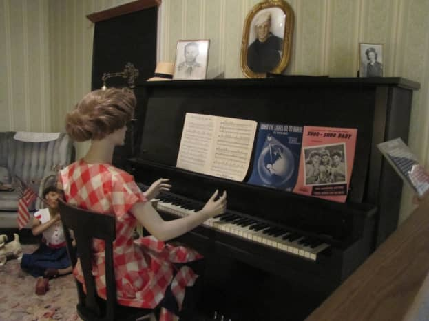 An example of ways a family entertained themselves in the 1940s. At Christmas time, they would gather around the piano to sing carols.