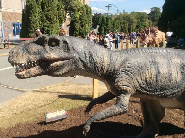 A dinosaur model on the road behind the Agrodome