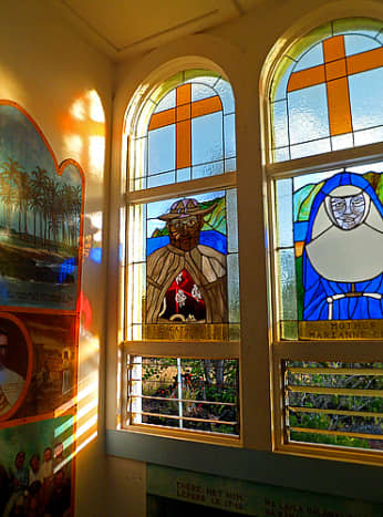 Stained glass windows (circa 1984) of Father Damien and Mother Marianne were designed and created by artist Ken Burkhardt.