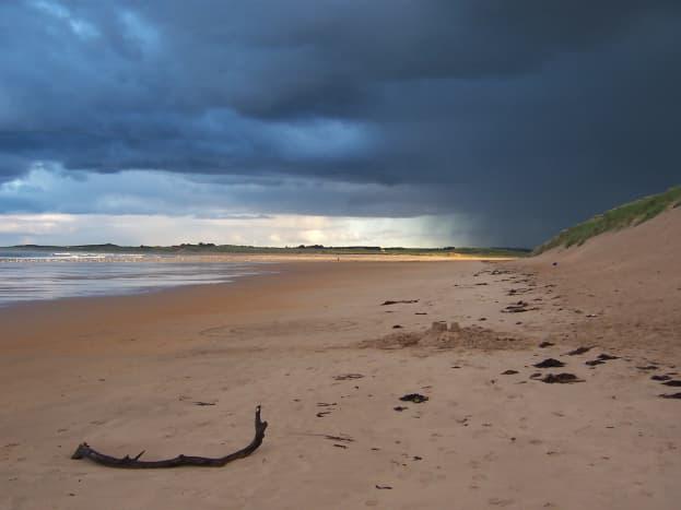 The Sandy beaches of Beadnell Bay under an evening sky