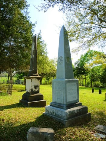 Col. Travis monument in foreground at Masonic Cemetery in Chappell Hill, TX