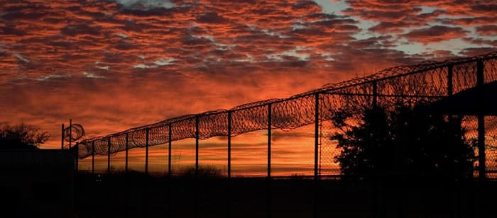 The sunset over a barbed-wire fence