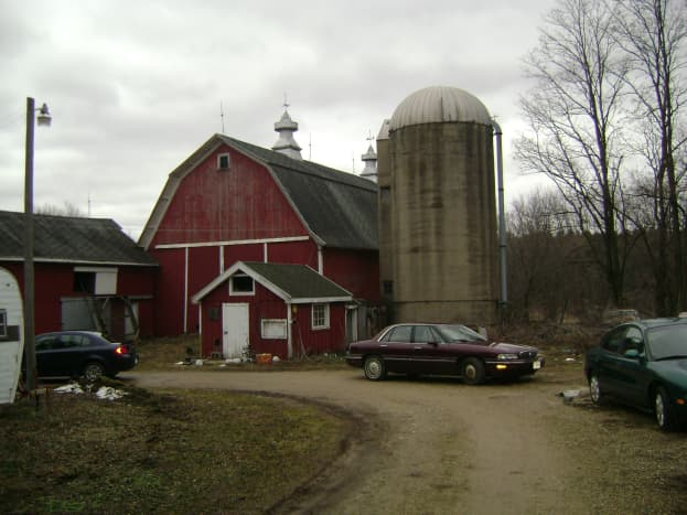The milkhouse is the small red building in front of the barn.  Taken in 2010.