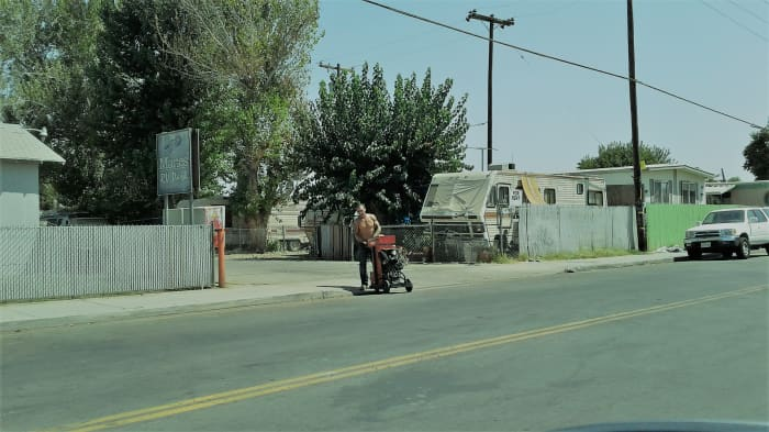 A shirtless man moves a strange machine along Beardsley Avenue
