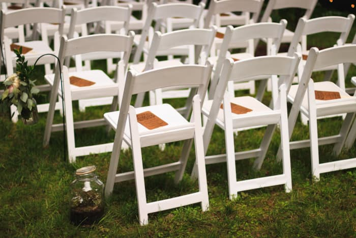 White wooden or resin folding chairs like these typically rent for around $2–5 per.
