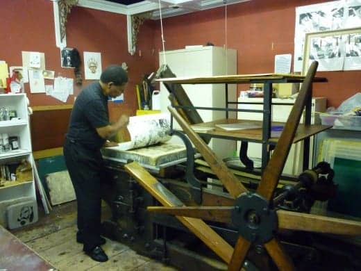 Criner pulls a lithography print off of a starwheel press from 1830.