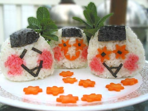 Slices of carrot, bits of nori (seaweed) and rice stained pink as decoration