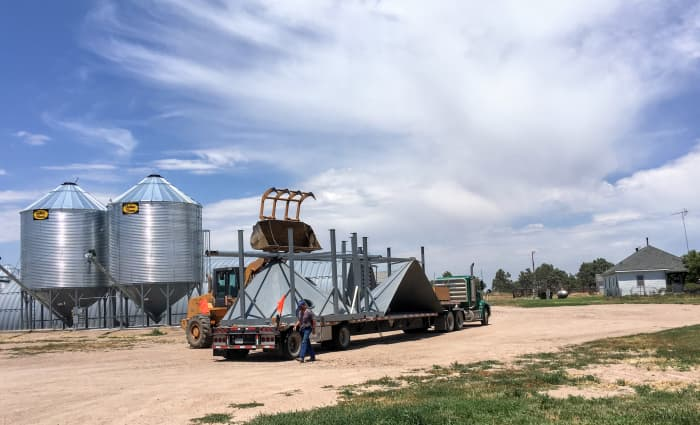 These hopper halves are about to be unloaded. In the background are two identical hoppers with 4,000-bushel grain bins.