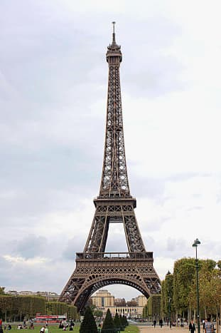The Eiffel Tower photographed from the green lawns known as the Parc du Champs de Mars which stretch out in front of the edifice