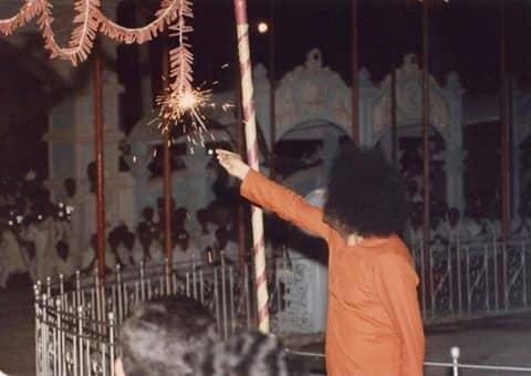 Swami lighting the 'garland crackers' in Prasanthi Nilayam.