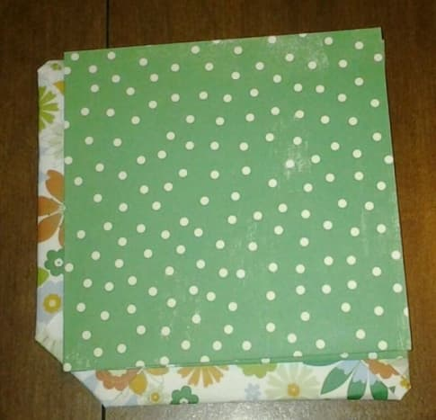 1. Take one folded page and use roller adhesive on one side. Press it into place on the inside of one cover as shown.